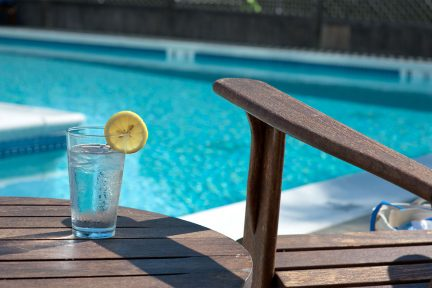 A glass of water with a lemon wedge on a table by the pool