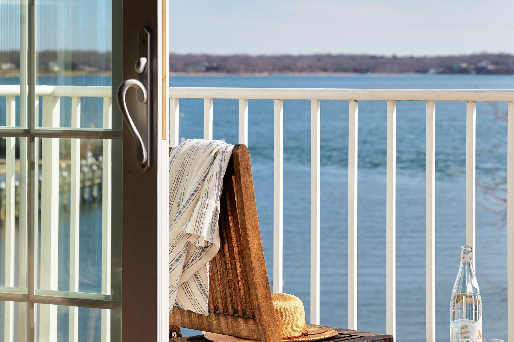 Tan hat sitting in chair on balcony overlooking Peconic Bay